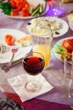 A glass of wine is on a served table. stock images