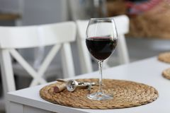 A glass of wine and some wine tools on a white wooden surface. Red wine. A glass of wine and some wine tools on a white wooden surface stock photo