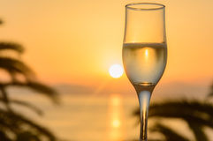 Glass of wine at sunrise at sea Royalty Free Stock Photography