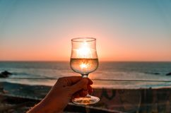 Glass of wine on the sunset. Glass of wine in the hand at the orange sunset royalty free stock photos