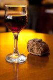 Glass of wine. On a table with bread in defocus Royalty Free Stock Photo