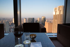 Glass of wine at the top with Tokyo skyline Royalty Free Stock Image