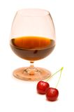 Glass of wine and two cherries Royalty Free Stock Photo