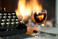 Glass of wine, typewriter and a fireplace Royalty Free Stock Image