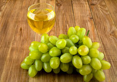 Glass of wine with a vine. On a wooden background Royalty Free Stock Image