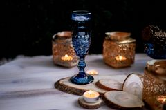 A glass of wine or water from a blue glass.Warm light of candles. Romantic dinner date. A glass of wine or water from a blue glass. Warm light of candles Stock Image