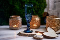 A glass of wine or water from a blue glass.Warm light of candles. Romantic dinner date. A glass of wine or water from a blue glass. Warm light of candles Stock Photography