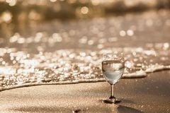 A glass of sparkling water on a sandy beach on a bright day.Style sepia tone. A glass of wine on the waxing background of soft drinks on the beach on a bright stock images