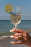 A glass of wine is in a woman's hand. Woman's hand decorated by seashells with a glass of wine Stock Photo