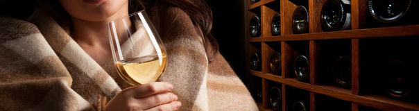 Glass of wine. In woman's hands on wooden wine rack background Royalty Free Stock Image