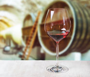 Glass of wine and wooden barrels in winery Royalty Free Stock Photo