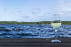 Glass of wine at a wooden pier. Luxury resort vacation concept. Blue Lake and green forest background.  stock images