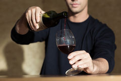 Glass of wine. Young man wants to drink a glass of wine royalty free stock photography