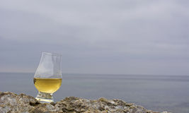 Glass with wisky on limestone rock with ocean and clouds in time Stock Photos