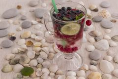 Glass With A Cooling Drink Of Berries And Ice. Misted Glass. Air Bubbles On Glass. A Slice Of Lemon On A Plate On The Background Stock Photography