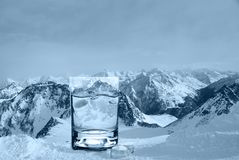 Glass With Water And Ice Cubes On The Background Of A Snowy Mountain Ridge, Cold Toning. Stock Images