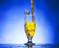 Glass withe yellow liqui. D on blue background Stock Photography