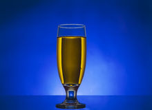 Glass withe yellow liquid. On blue background Stock Images