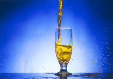 Glass withe yellow liquid. On blue background Stock Photos