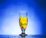 Glass withe yellow liquid. On blue background Royalty Free Stock Images