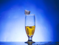 Glass withe yellow liquid. On blue background Royalty Free Stock Photo