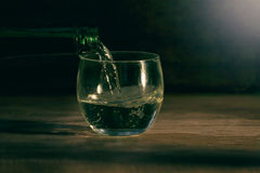 Glass on wood table dark background Royalty Free Stock Image