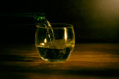 Glass on wood table dark background Stock Photos