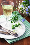 Glass with woodruff liquor on wooden table. And antique silverware Stock Photography
