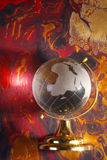 Glass world globe on abstract. A view of a glass world globe reflecting light onto a background of original, colorful, abstract design Stock Image