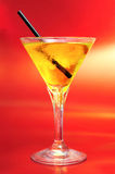 A glass with a yellow cocktail. On a red background stock photos
