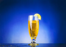 Glass yellow liquid. On blue background Royalty Free Stock Photos