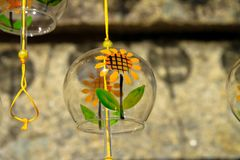 Glass with yellow sunflowers hanging from yellow rope on wooden stock photography