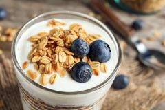 Glass with yogurt, berries and granola. Closeup royalty free stock images