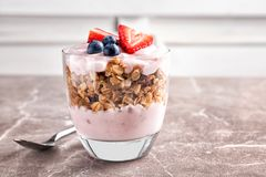 Glass with yogurt, berries and granola. On table Stock Image