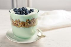 Glass with yogurt, berries and granola. On table Stock Images