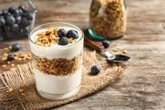 Glass with yogurt, berries and granola. On wooden table royalty free stock photos