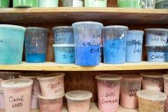 Glassa delle terraglie nei colori differenti in recipienti di plastica sugli scaffali immagine stock