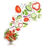Glassalatschüssel im Flug mit Gemüse: Tomate, Pfeffer, Stockbild