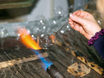 Glassblower heats the glasspiece Royalty Free Stock Photos