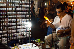 Glassblower making new glass products for sale during night market Royalty Free Stock Photo