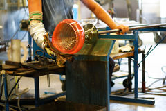 Glassblower shaping a vase. Traditional Swedish glass blowing. A hot glowing vase is rolled on its blowing shaft, while a glassblower shapes it Royalty Free Stock Images