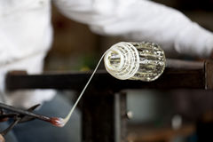 Glassblower shaping wrapping molten glass Royalty Free Stock Image