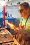 Glassblower at work. A professional glassblower performs a live demonstration, using his skills to create handmade works of art with molten glass Stock Photos