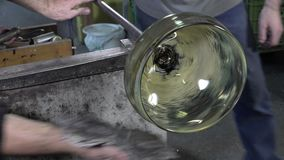 Glassblower working in his workshop stock video footage