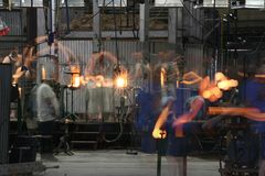 Glassblowers in movement creating glass articles Royalty Free Stock Photography