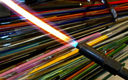 Glassblowers Torch and Colored Glass. Vinatage lampworker torch with colored glass working rods in background stock images