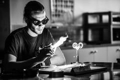Glassblowing młody człowiek Pracuje na pochodnia płomieniu z Szklanymi tubkami fotografia stock