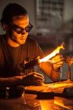 Glassblowing młody człowiek Pracuje na pochodnia płomieniu z Szklanymi tubkami obrazy stock