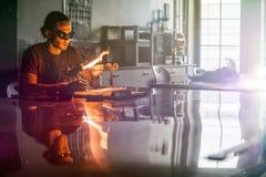 Glassblowing młody człowiek Pracuje na pochodnia płomieniu z Szklanymi tubkami obraz royalty free