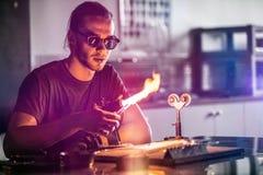 Glassblowing młody człowiek Pracuje na pochodnia płomieniu z Szklanymi tubkami zdjęcie stock